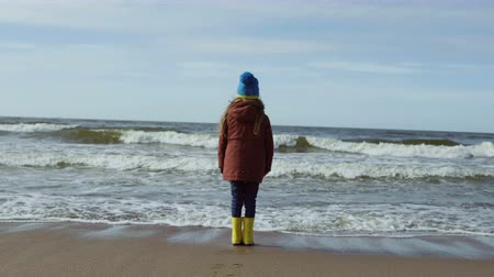 gumboots : Happy child standing on shore of the sea and looking into the distance. Smiling little girl run away from wave, smiling.