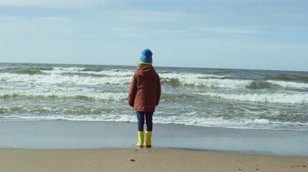 gumboots : Lonely little girl in bright yellow rubber boots standing on the sandy beach and resting. Cute female looks at the waves Stock Footage