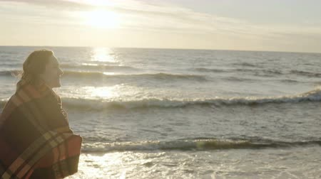 растягивается : Young happy woman walking on beach on sunset. Beautiful female goes on shore of the sea with plaid in stretched arms. Стоковые видеозаписи
