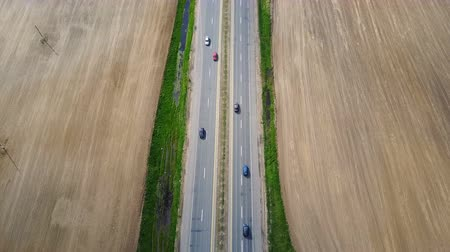 országúti : Aerial drone shot of empty motorway. Car driving through the road at the countryside, through the field.