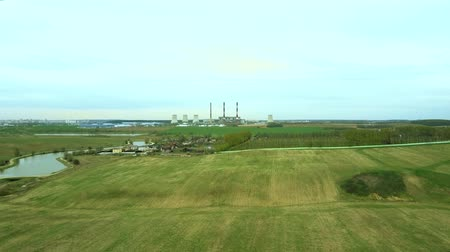 radioaktivní : Aerial view of the green field and industrial factory. Flight over the plant producing thermal energy with pipes. Dostupné videozáznamy