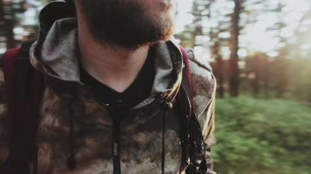 hnědožlutý : Close-up view of man with beard standing in the forest in the morning. Male in camouflage with backpack at nature.