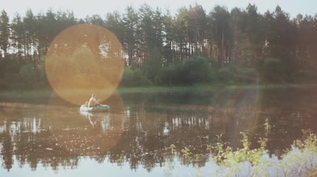 fisher : Two man fishing together in inflatable boat in the morning. Beautiful landscape of the forest, lake and sun rays. Stock Footage
