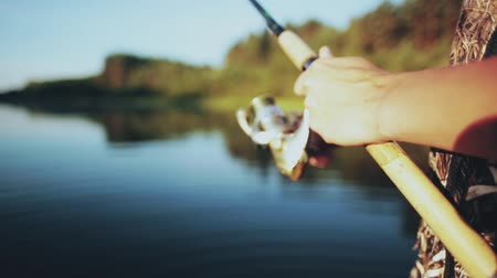 jangada : Close-up view of male hands holding the fishing rod. Young Fisher man twisting the rod with spinning reel. Vídeos