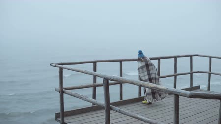 gumboots : Back view of little girl in rubber boots and plaid standing on wooden pier near the sea. Alone child in foggy windy day.