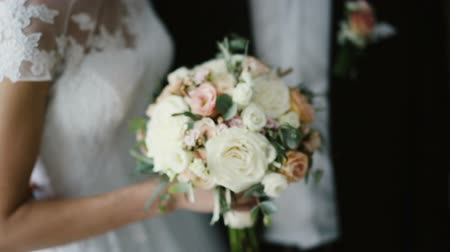 smokin : Close-up view of young beautiful bride and room. Man and woman with bouquet standing together after wedding.