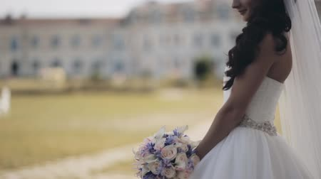 новобрачный : Attractive brunette bride standing in nature wearing the wedding dress. Beautiful woman holds bouquet, waits ceremony. Стоковые видеозаписи