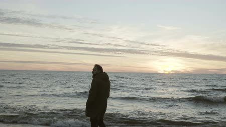 endure : Young attractive man standing on the shore of the sea and looking on sunset. Male enjoying the landscape at beach. Stock Footage
