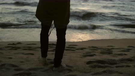 endure : Lonely man walking on the shore of the sea and enjoying the sunset. Young male admires the waves on the beach.