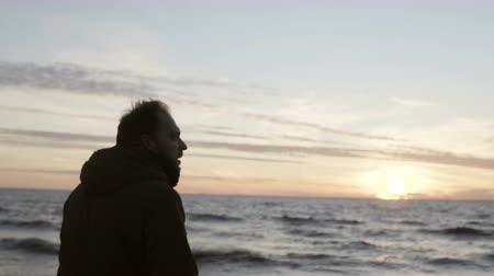 onda : Young man walking in the shore of the sea alone and looking on the waves. Male enjoying the sunset on the beach.