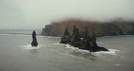 racek : Copter turning around the troll toes cliffs on the sea in Iceland. Beautiful black volcanic beach and mountain in fog.