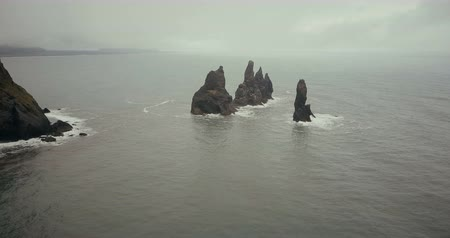 arctic animals : Aerial view of the troll toes mountain in the water in Iceland. Copter flying around the cliff in sea in foggy day.