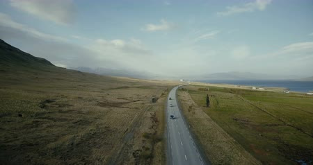 придорожный : Aerial view of the ocean and mountains valley. Cars riding on the countryside road with field around.