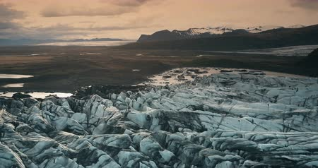glacier point : Aerial view of the ice lagoon on sunset. Copter flying over the glacier Vatnajokull with volcanic ash in Iceland.