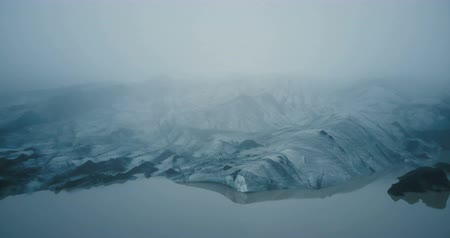 glacier point : Aerial view of the white glacier Myrdalsjokull with black ash in Iceland. Eternal ice in fog in mountain.