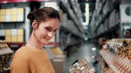 corredor : Young attractive brunette girl at the store chooses bright gold Christmas decor. Vídeos