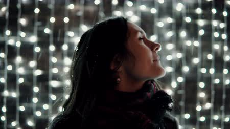 city park : young attractive woman enjoying falling snow at Christmas night in front of the decorative wall full of sparkling lights