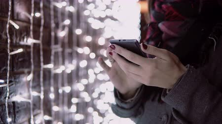 lanterns : close-up hands young woman using smartphone in the falling snow at Christmas night standing near lights wall,