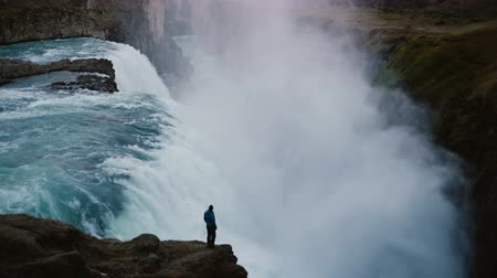 gullfoss : Beautiful view of the man standing on the edge of the rock and looking on the Gullfoss waterfall in Iceland.