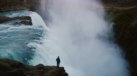 meditativo : Scenic landscape of the lonely man standing on the edge of the mountain and looking on the Gullfoss waterfall in Iceland