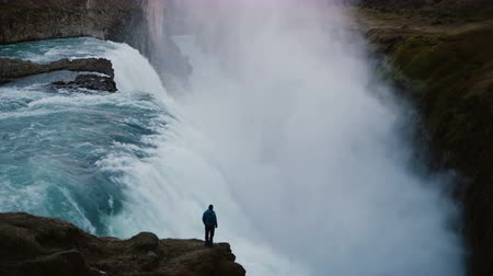 gullfoss : Time lapse of landscape of the Gullfoss waterfall in Iceland and man standing on edge of the cliff, enjoying the view.