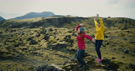 reykjavik : Aerial view of the beautiful landscape in Iceland, lava field covered moss. Two woman dance and jump on the mountain.