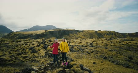 reykjavik : Aerial view of the two woman in the lava field in Iceland raise hands. Happy tourists send air kiss to copter.