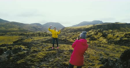 bumps : Copter filming the tourists having the photoshoot in the mountains. Two woman taking photo in lava field in Iceland. Stock Footage
