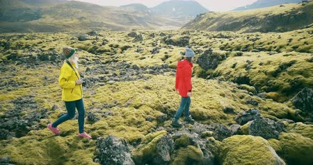 bumps : Copter flying around two woman on lava field in Iceland. Tourists with camera walking on the nature and taking photos.