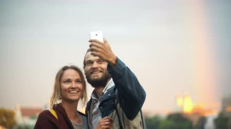 sırt çantasıyla : Young couple taking selfie photos with rainbow on background. Cheerful man and woman use the smartphone technology. Stok Video