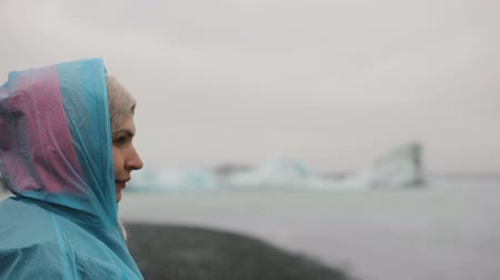 glacier point : Portrait of young woman in raincoat standing in ice lagoon in Iceland. Female looks something unexpected and jumps.