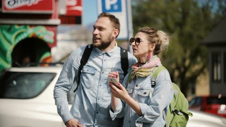 reykjavik : Young stylish couple standing on the city centre and use smartphone. Man and woman look at the map to find direction Stock Footage