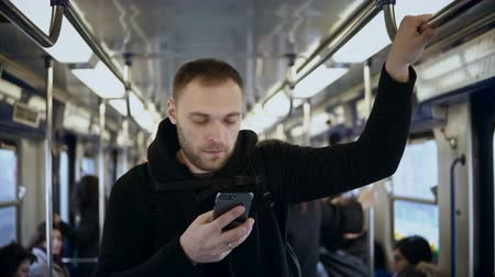 fare : Young handsome man uses the smartphone in public transportation, in metro. Male surfing the Internet with touchscreen