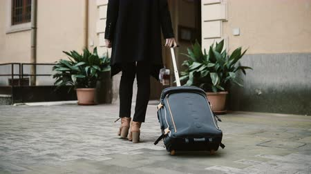 bagagem : Beautiful woman with suitcase going away from apartment. Businesswoman with baggage are going to trip, vacation. Vídeos
