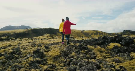 desert life : Aerial view of two woman walking on the lava field in Iceland. Tourists female hiking on the mountains covered moss.