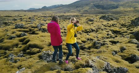 hardened lava : Aerial view of the two happy woman standing on the rock and having fun, dancing. Lava field in Iceland covered moss.