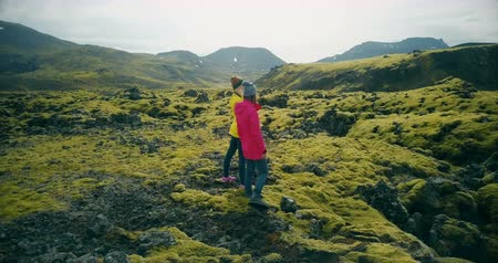 hardened lava : Aerial view of two woman walking on the lava fields in Iceland. Tourists enjoying the landscape, exploring the territory Stock Footage