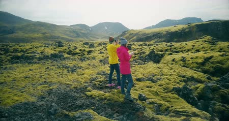 hardened lava : Aerial view of two tourists woman walking on lava fields in Iceland and making photos. Girls use smartphone and camera.