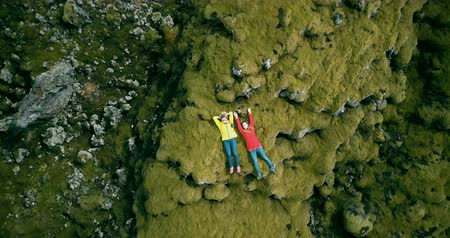 vulkán : Aerial view of two happy tourists woman lying on the lava field in Iceland. Copter flies up from close-up to long shot
