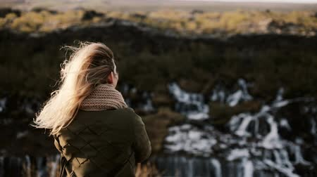 hipster : Back view of young blonde woman standing on the cliff and looking at Barnafoss waterfall in Iceland, touching hairs.