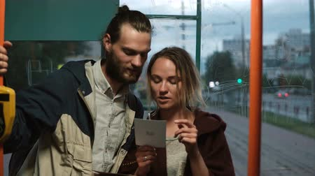 tramwaj : Young happy couple in a public transport, in tram holding the card. Man and woman having fun together in evening. Wideo