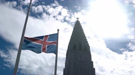lutheran : Beautiful view of the beautiful church Hallgrimskirkja in Reykjavik, Iceland and national flag waving on the wind.