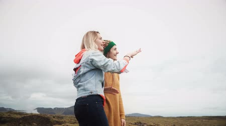 hardened lava : Two tourists female standing on the lava field in Iceland and pointing with finger on something. Happy woman talking.