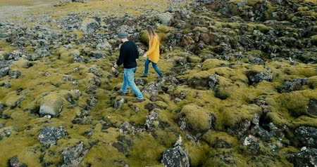 hardened lava : Aerial view of young stylish couple walking through the volcanic lava field in Iceland. Man and woman go to their car. Stock Footage