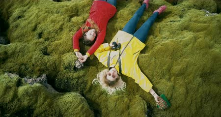bumps : Aerial top view of the two happy woman lying on the soft moss in lava field in Iceland. Tourists resting on nature.