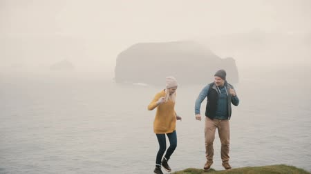 islandia : Young happy couple dancing near the sea. Tourists man and woman having fun together after hiking on a mountain. Wideo