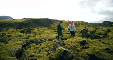 hardened lava : Aerial view of young couple walking on the volcanic lava field in Iceland. Man and woman enjoying the landscape.
