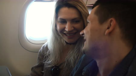 avançar : Young beautiful woman and handsome man sitting on the plane near the window and talking, laughing together.