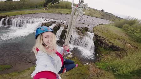 karabély : Selfie on action camera of young beautiful woman flying downhill on bungee through the rope way over the river.
