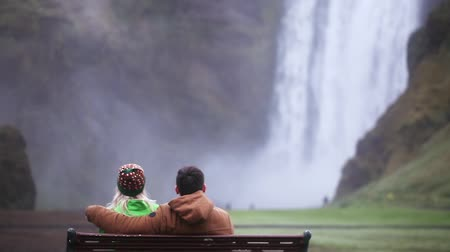 skogafoss : Back view of young couple sitting on the bench and enjoying the beautiful view of Skogafoss waterfall in Iceland.